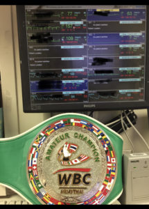 Carody's amateur WBC Champion belt in front of a screen displaying patient vitals at her job as a registered nurse
