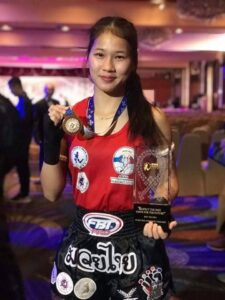 Buakaw Mor Kor Chor Chaiyaphum in 2018. Pictured with her Best Wai Kru Award and gold medal from the Asian Muaythai Championships. lumpinee first woman females muay thai muay ying
