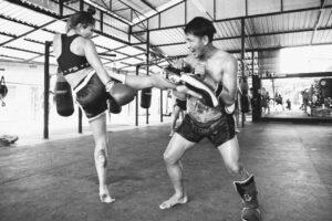 woman kicking thai pads in phuket with trainer muay thai