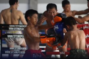 kids sparring trainer watching and teaching muay thai camp